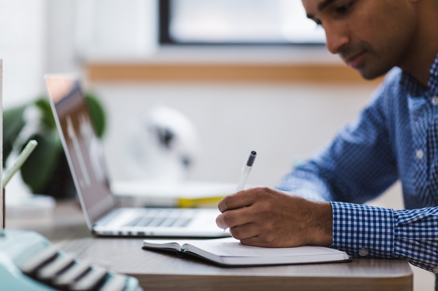 A man is writing about the resume writing tips he can use in his notebook