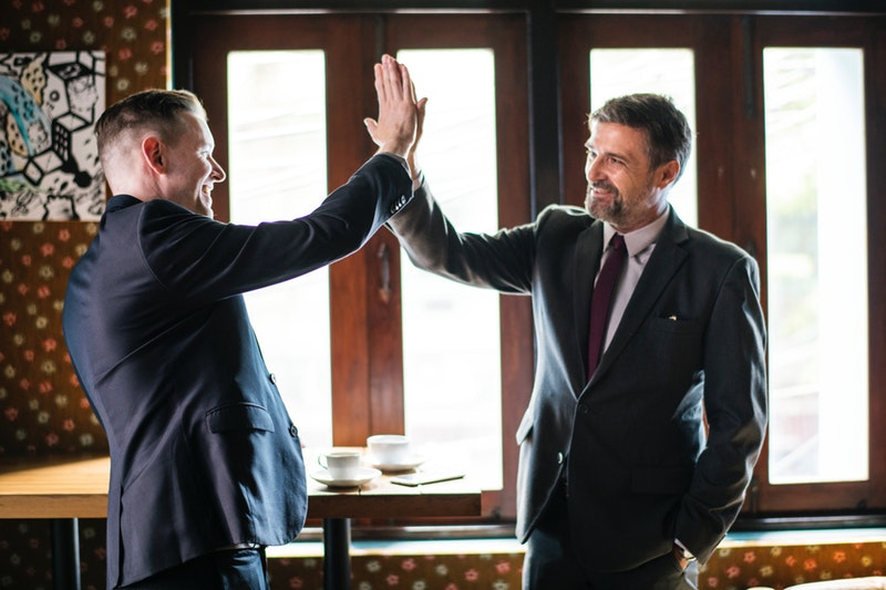 An employee doing a high five with his boss because he followed tips on how to impress him
