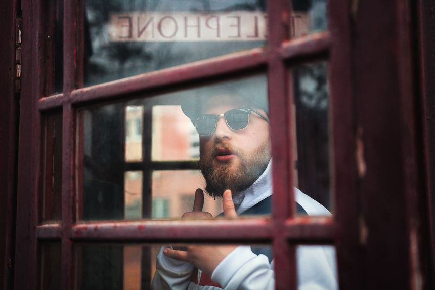 A man follows up after his interview inside a telephone booth