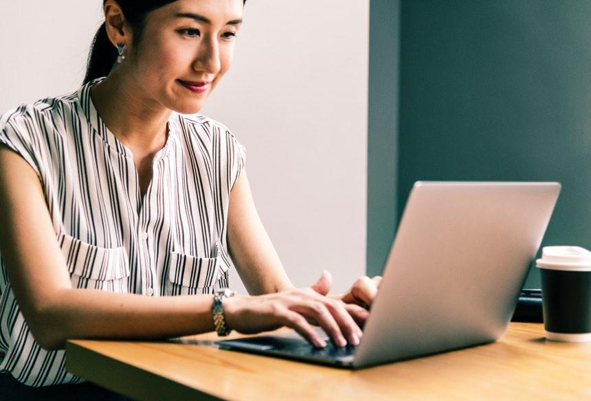Smiling resume writing career woman typing on her laptop