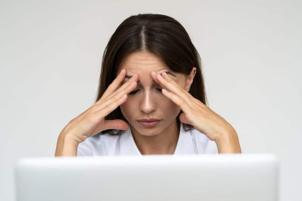 a woman whose hands are placed in her head as a sign of work stress