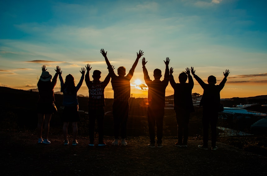 A team raising their hands while waiting for the sunset to promote workplace diversity
