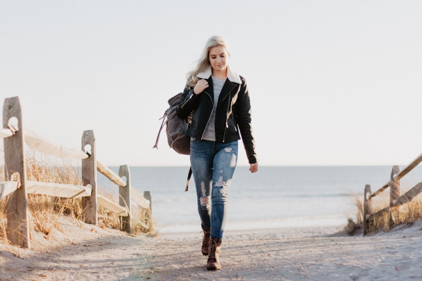 A woman carrying a backpack while walking towards new career opportunities because of layoffs