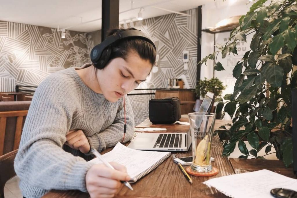 Young man in a cafe researching where to put education section in his resume