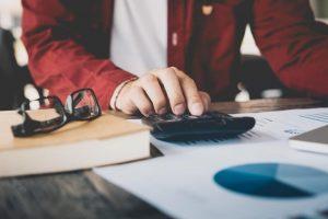 Man computing his salary requirements while writing a resume