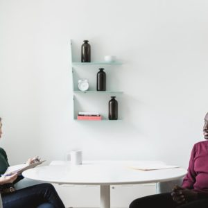 A male job seeker answers job interview questions from a female interviewer in a meeting room