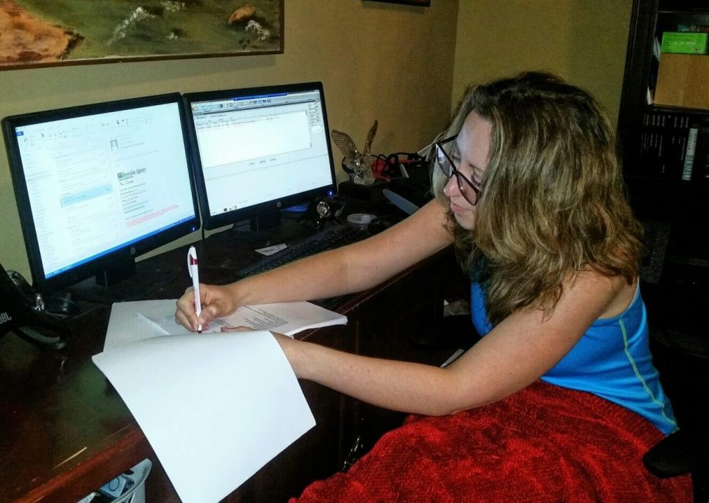Woman rewriting her copy editor resume while working