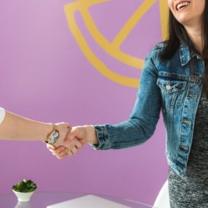 Woman shaking hands of another to signify accepting a job offer