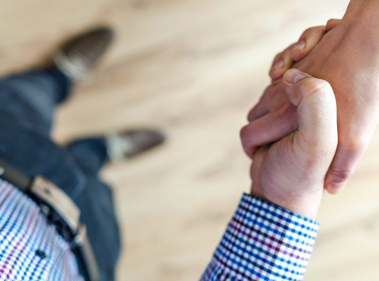 A man wearing checkered polo shaking hands with a coworker to promote workplace likability