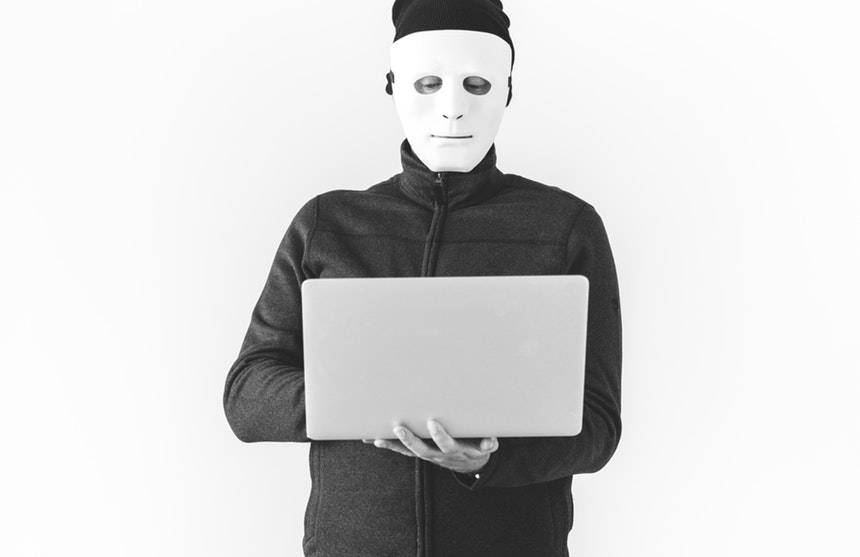 masked man holding a laptop while creating ripoff reviews