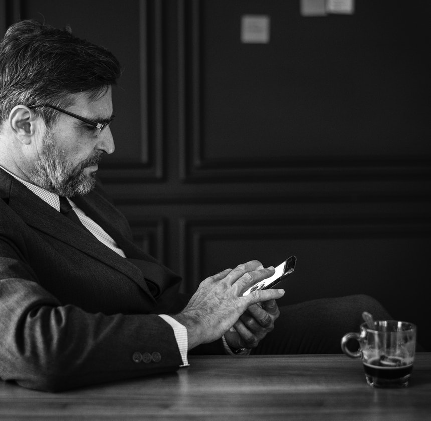 man in suit browsing for top executive resume writers in his smartphone