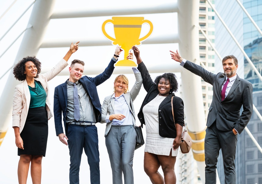five top executive resume writers raising a cardboard trophy