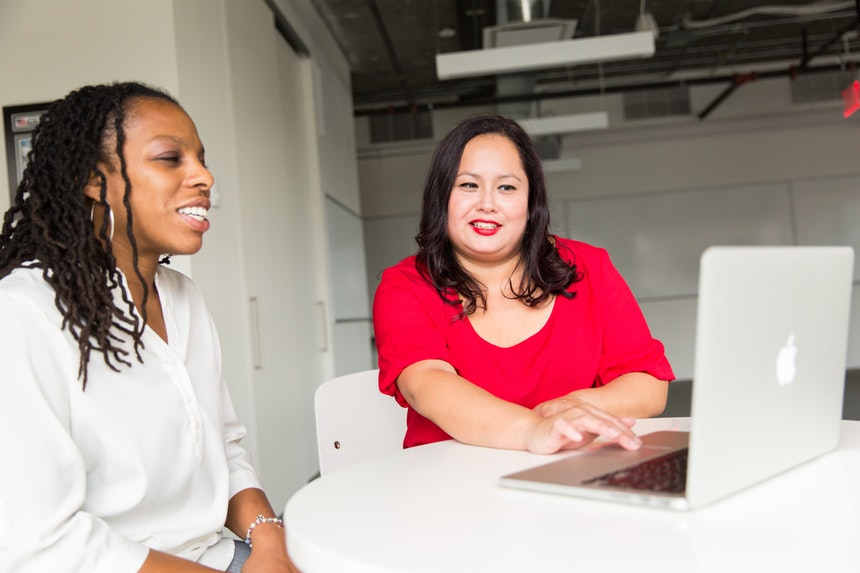 two woman sitting in front of a laptop teaching each other how to make a resume