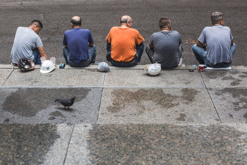 Five mean seated on the pavement depicting the search for in demand jobs