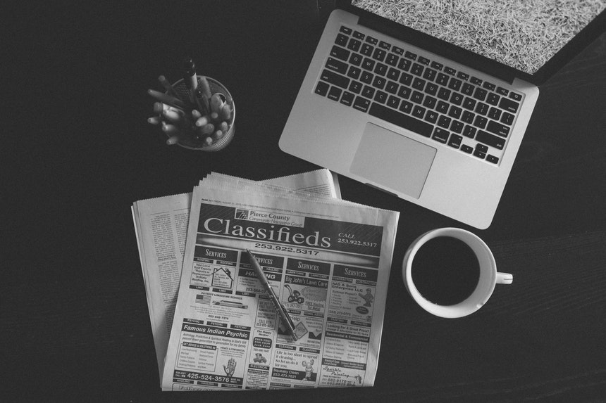 grayscale image of newspaper classified ads and laptop for resume writing