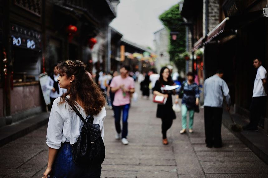 Woman walking in the streets of Hong Kong looking for industries for skilled foreign workers