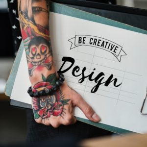 tattooed arms carrying creative resumes and portfolio