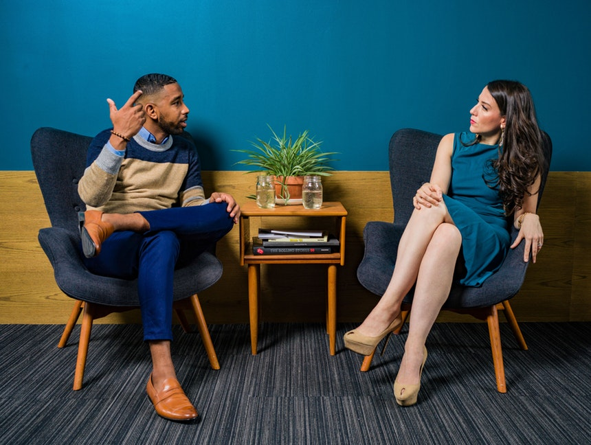 A man and woman sitting while discussing about career advice for millennials
