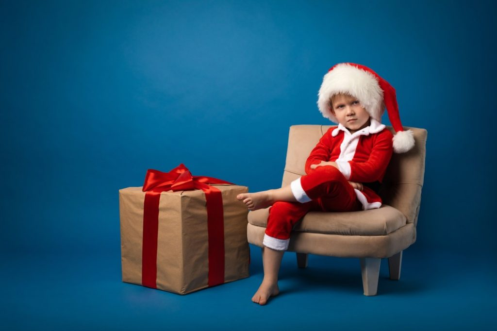Angry kid sitting and wearing Santa costume with a Christmas gift on his side