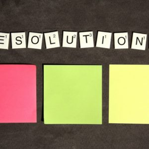Three sticky notes and scrabble tiles to show listing of career resolutions