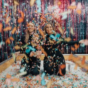 Two woman enjoying the party game ideas with a lot of colorful confetti