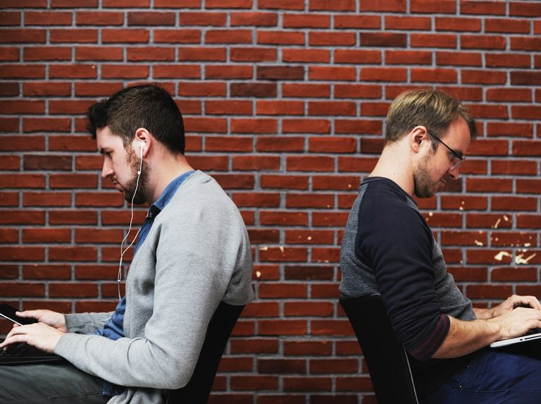 Two men sitting back to back each other while searching for job search tips