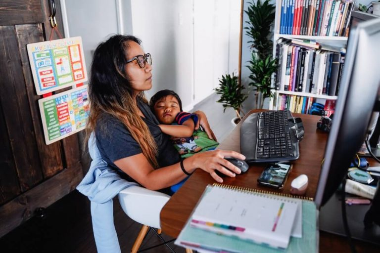Young mom with sleeping kid looking for mom jobs online