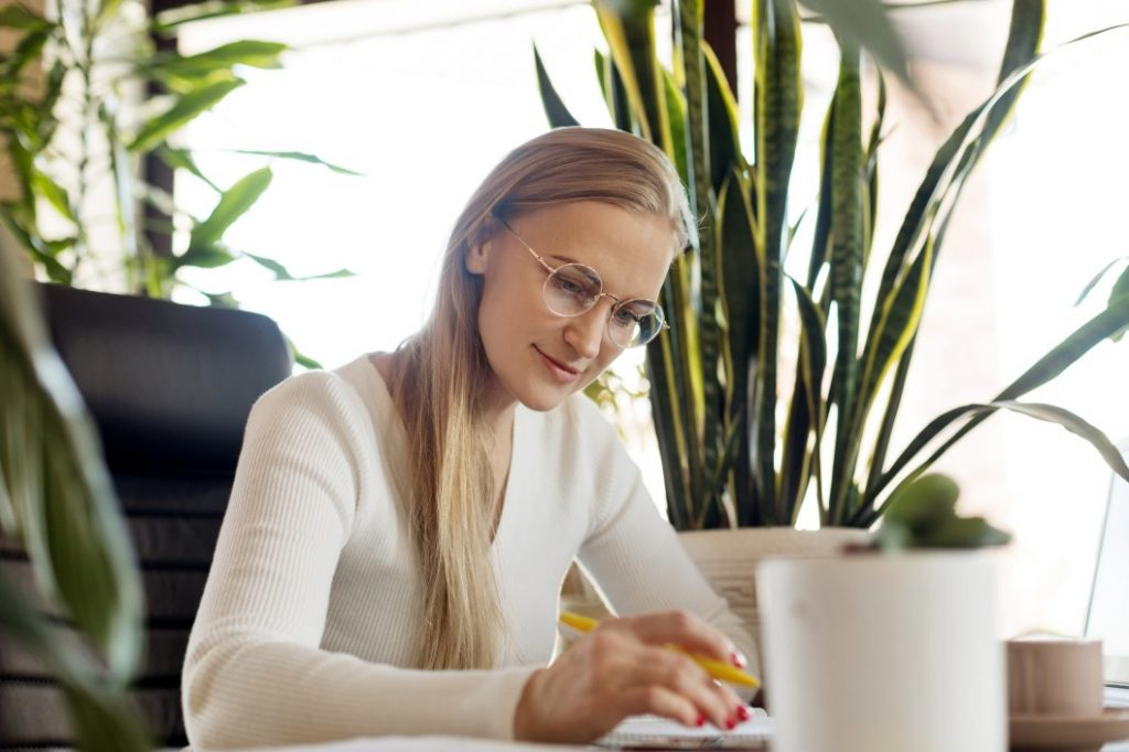 a woman sitting on her working desk and happy with her career