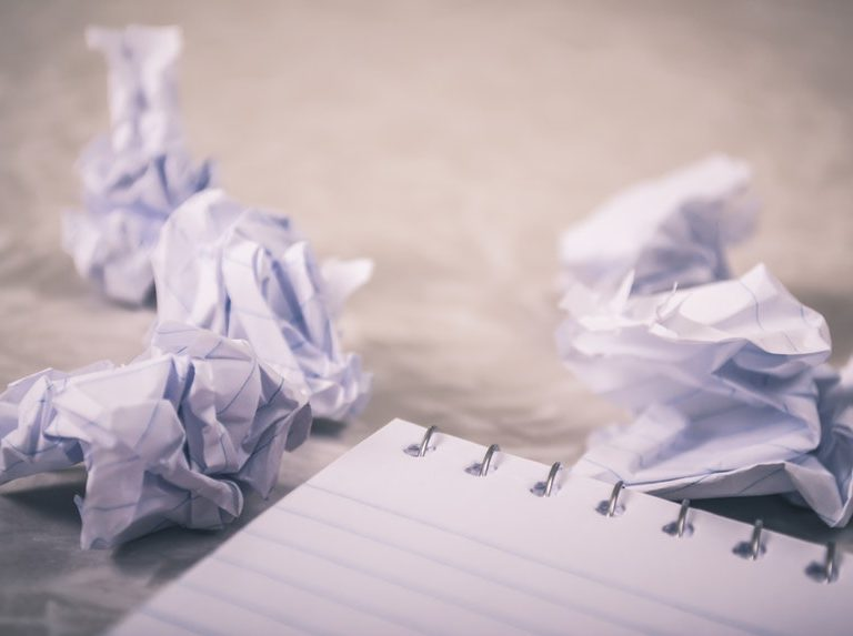 three crumpled paper with horrible resume mistakes written next to a notebook