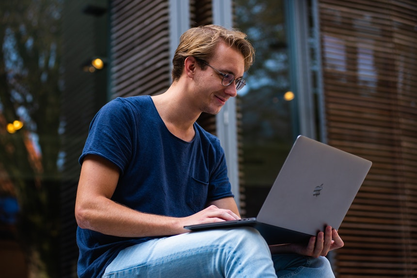 a happy man holding a laptop while writing the best resume