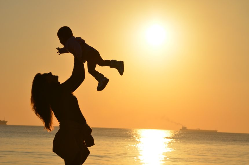 A working mother carrying her child along the shores of a beach