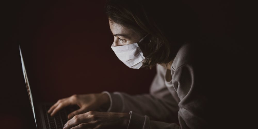 Woman with face mask using laptop during coronavirus pandemic