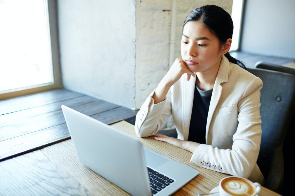 One of the professional resume writers assessing a client's resume on her laptop