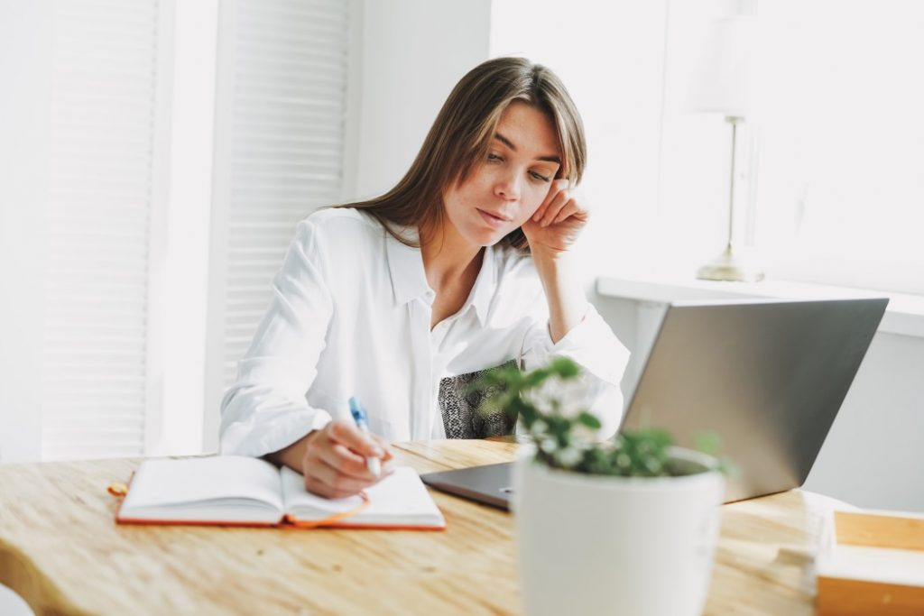 woman searching about words to describe yourself in a resume and writing it in a notebook