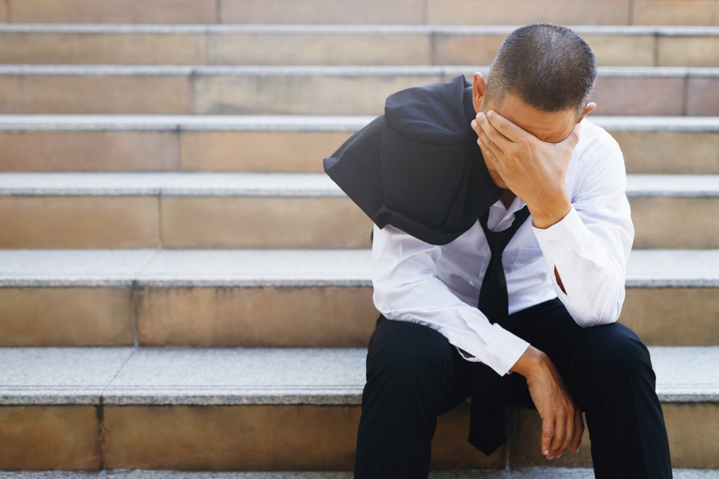 a man in suit feeling depressed due to job loss