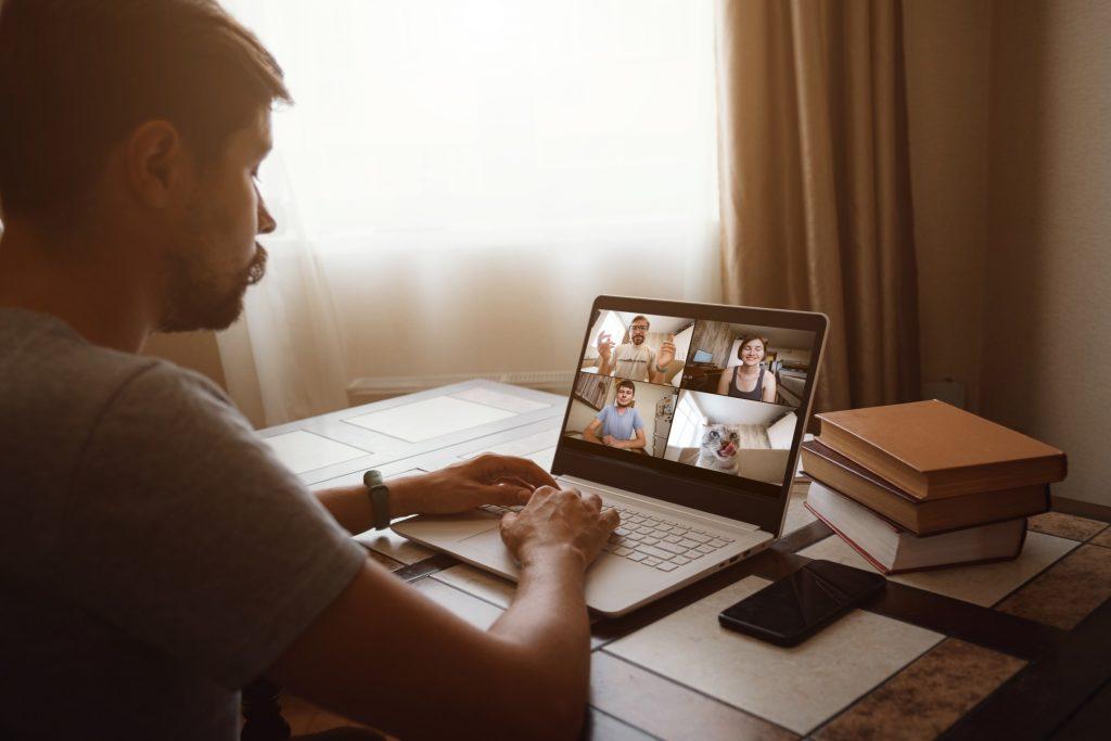 man talking to his team online via zoom meeting