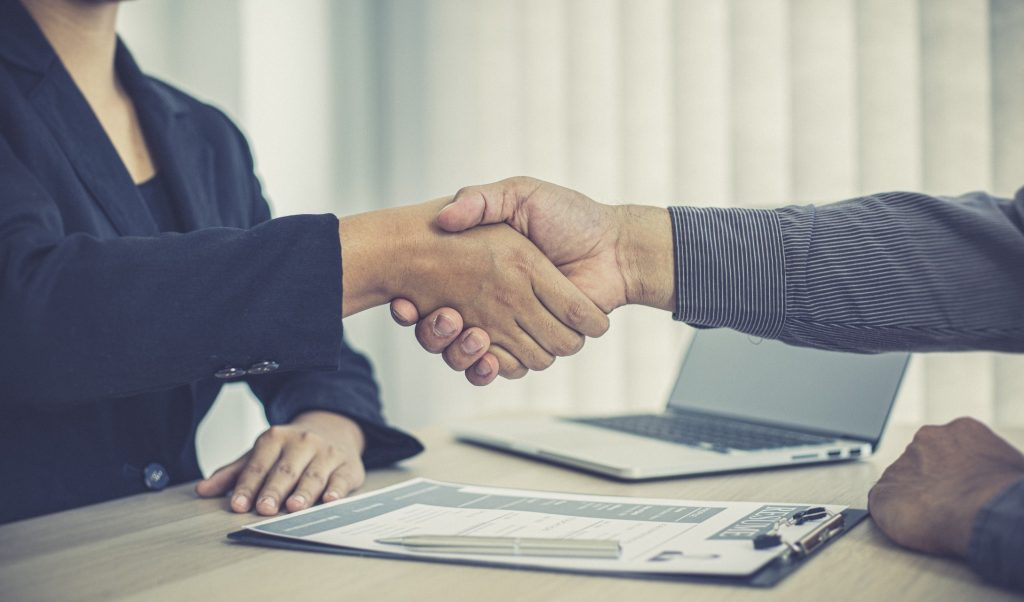 hiring manager and job applicant shake hands as the latter accepts the job offer