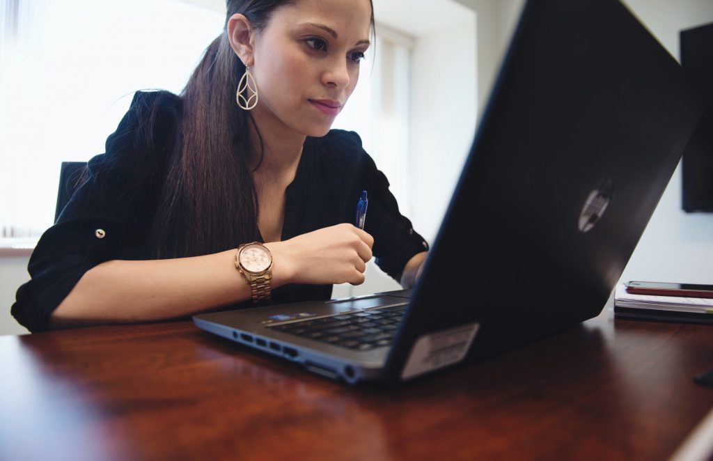 woman job seeker typing her federal resume on her laptop