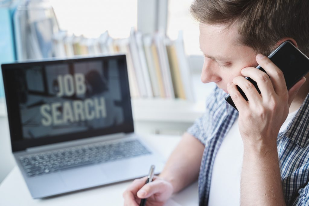 job seeker looking for posts online while talking on the phone